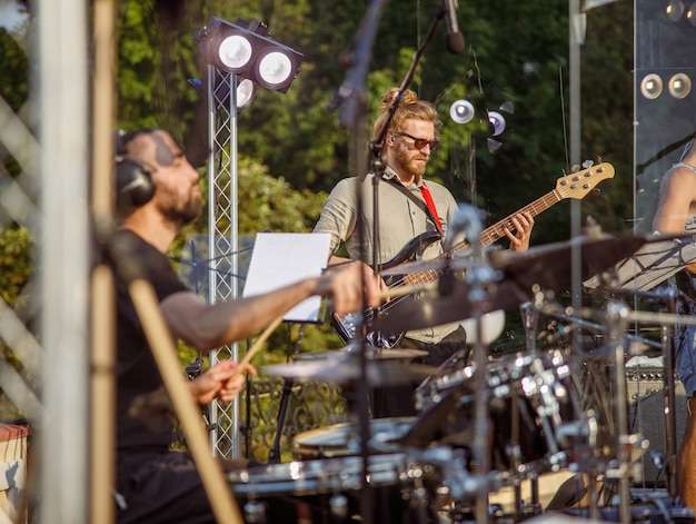 Bearded man guitarist and drummer playing melody at outdoor concert stage