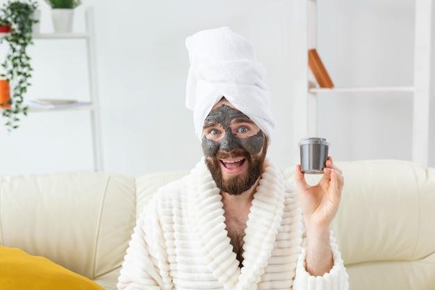 黒粘土の男性のスキンケアユーモアから作られた彼の顔の化粧マスクを楽しんでいるひげを生やした男と