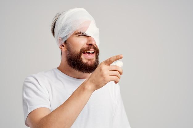 흰색 티셔츠 두통 병원 의학에서 수염 난된 남자 머리 부상. 고품질 사진