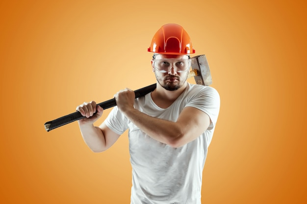 Bearded man in a helmet holds a sledgehammer on an orange background