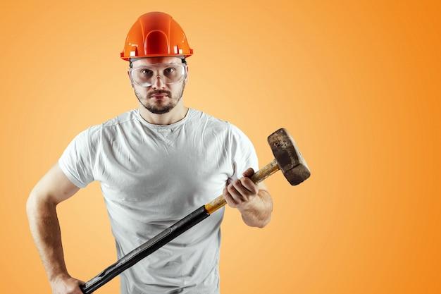 Bearded man in a helmet holds a sledgehammer on an orange background