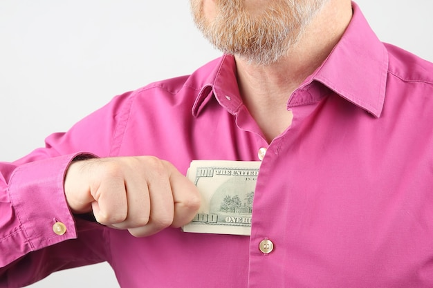 수염 난 남자는 그의 셔츠에 돈을 숨 깁니다.