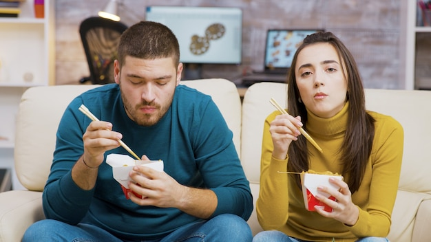 Bearded man and his girlfriend eating noodles with chopsticks while watching tv.