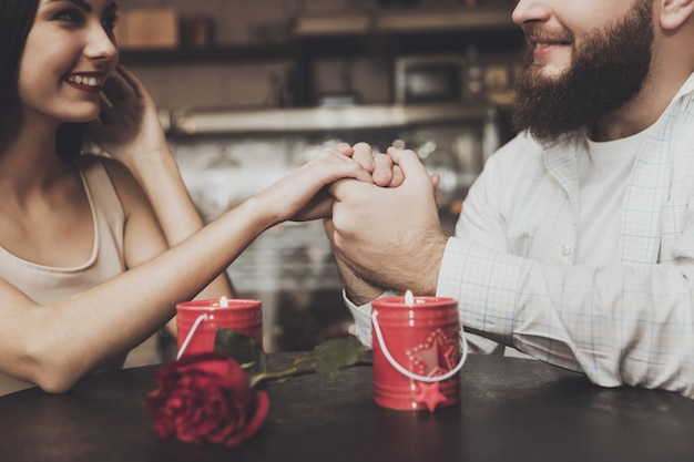 Bearded man hold the hand of a beautiful girl