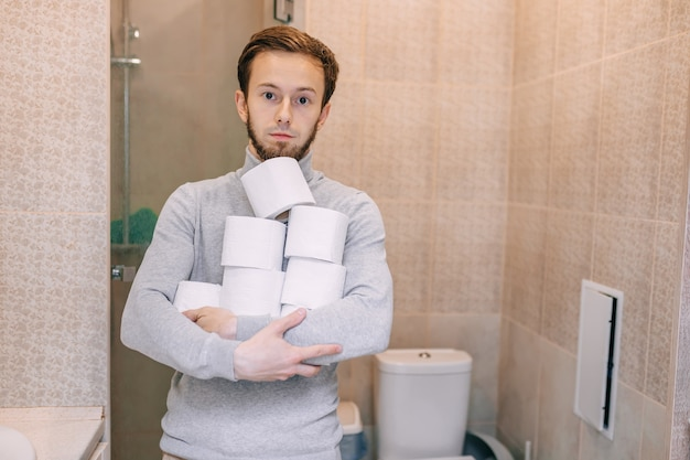 Bearded man hold toilet paper. the guy is suffering from diarrhea.