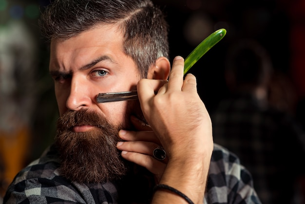 Бородатый мужчина приставил бритву к щеке