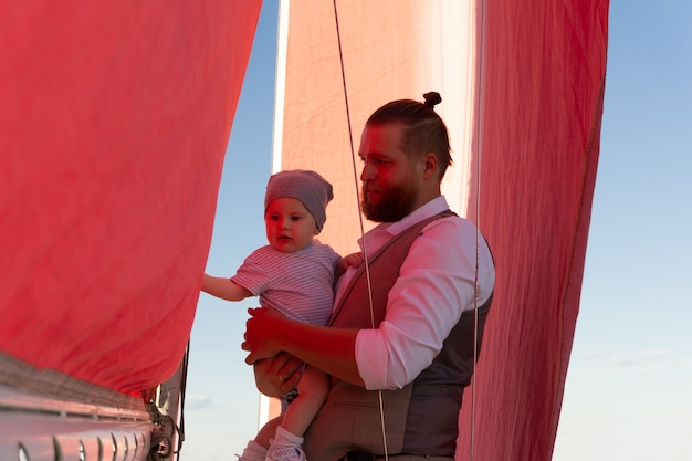 Bearded man holding a baby in his arms against the background of blue sky and a ship mast