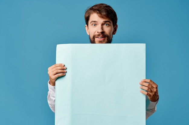 Bearded man holding a banner advertising blue in front of him