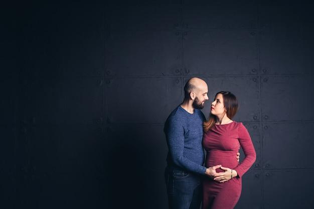 妊娠中の女性の腹を保持しているひげを生やした男