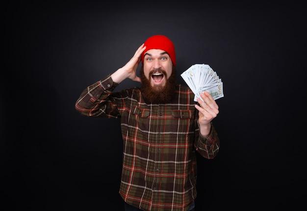Бородатый мужчина держит кучу долларов над изолированной стеной, очень счастлив и взволнован, выражение победителя празднует победу кричать с большой улыбкой и поднятыми руками