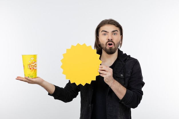 Bearded man holding bucket of popcorn and paper sun.