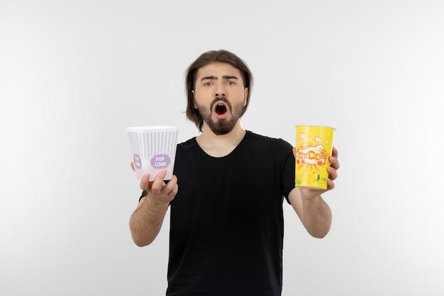 Бородатый мужчина держит ведра попкорна.