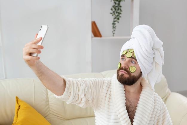 수염을 기른 남자가 집에서 얼굴 스파에 오이 조각을 들고 남성 개념을 위한 피부 관리