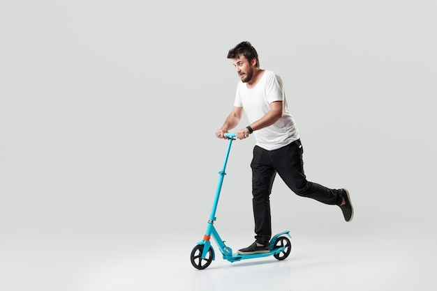 Bearded man holding the electric scooter and riding it while feeling delighted