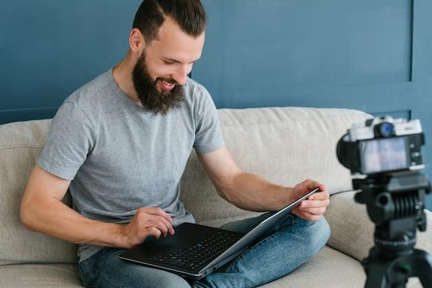 ノートパソコンを持って三脚にカメラを使って自分のビデオを撮影しているひげを生やした男。現代のテクノロジーとブログのフリーランスの仕事のコンセプト。