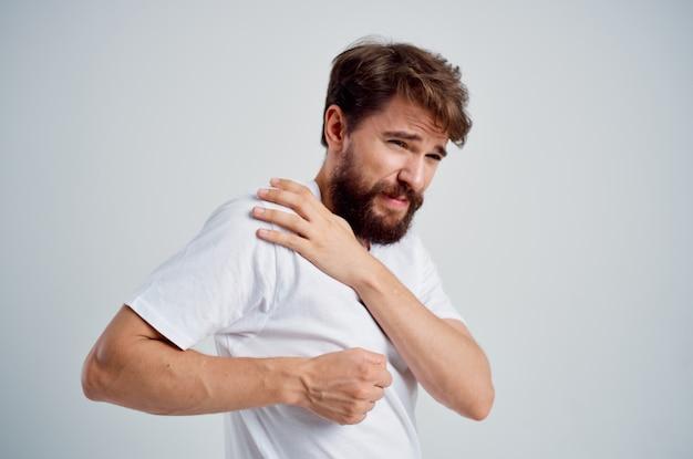 Бородатый мужчина держит проблемы со здоровьем артрит шеи светлый фон. фото высокого качества