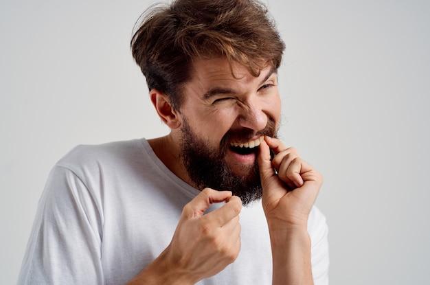 歯の明るい背景の痛みに直面するために保持しているひげを生やした男