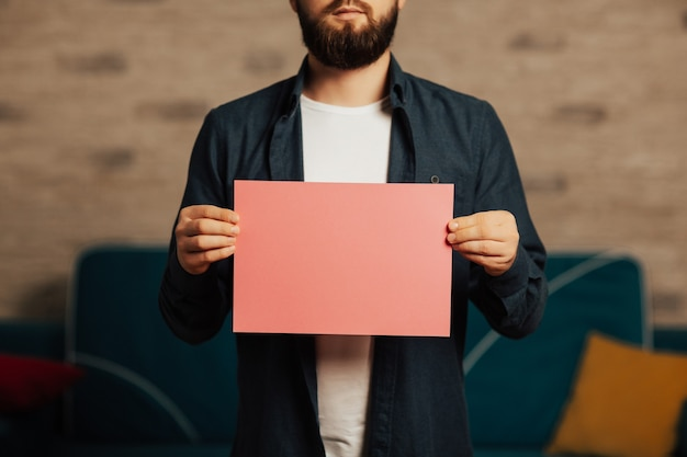 Bearded man holding pink paper with copy space.