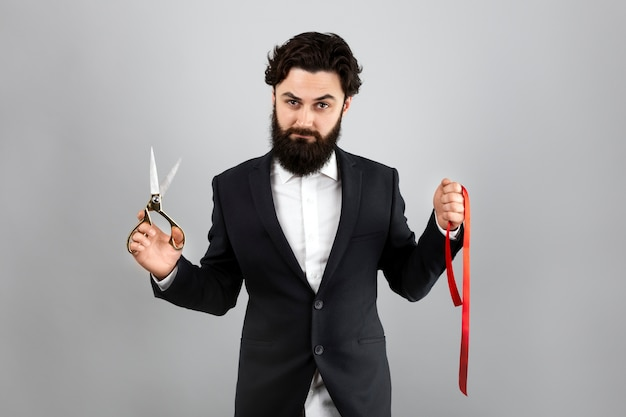 Bearded man holding  red ribbon and scissors over gray wall, grand opening
