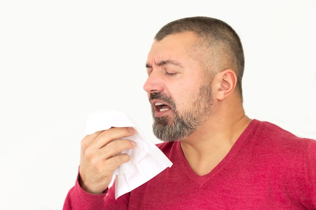 Bearded man holding a tissue and sneezing isolated on white background