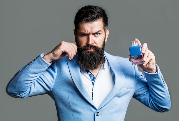 Bearded man holding up bottle of perfume. fashion cologne bottle.