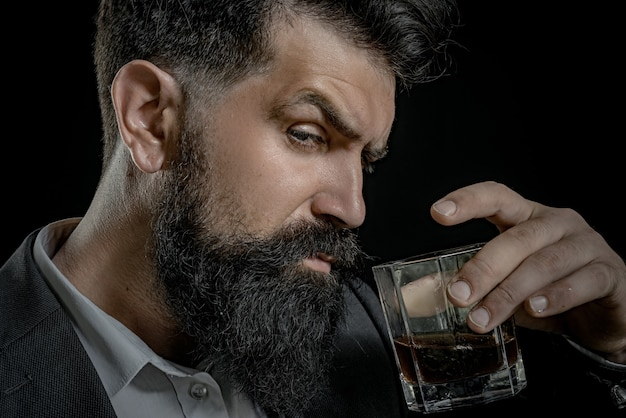 Bearded man holding whisky cocktail in glass  close up portrait alcohol drink