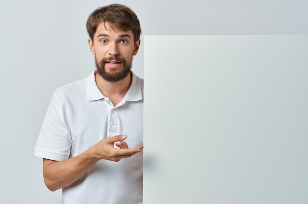 白いバナーコピースペース広告エグゼクティブポスターを保持しているひげを生やした男。