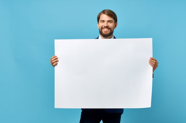 Bearded man holding white mockup poster copy space blue background