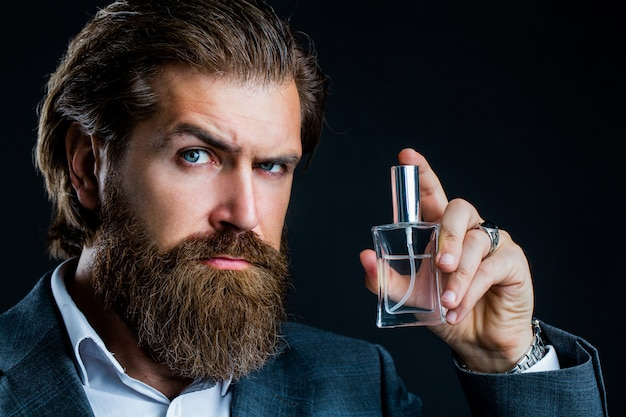 A bearded man holds a bottle of perfume.