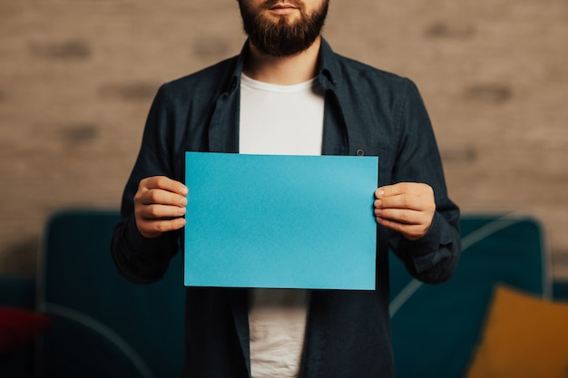 Bearded man holds in front of him a blue mockup.