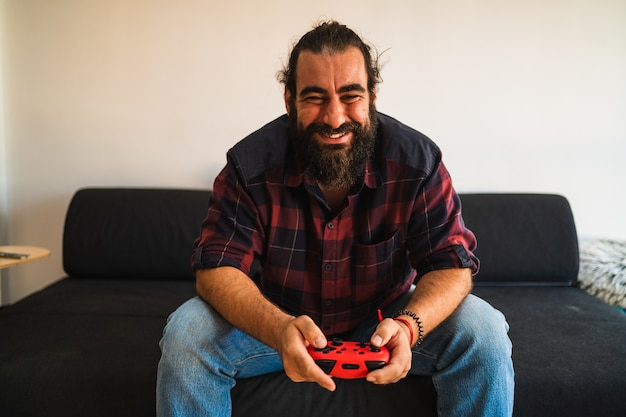 Bearded man holds a gaming controller while playing videogames