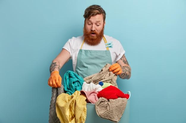 Bearded man holds laundry basket, overwhelmed by household chores