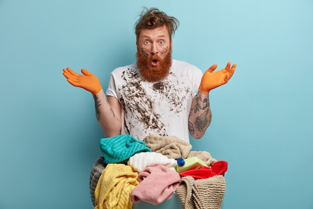 Bearded man holds laundry basket, overwhelmed by household chores