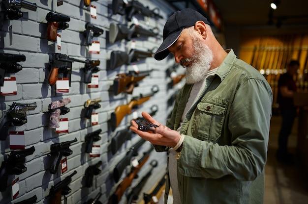 ひげを生やした男は銃店のショーケースでピストルを保持しています。武器屋のインテリア、弾薬と弾薬の品揃え、銃の選択、射撃の趣味とライフスタイル、護身術