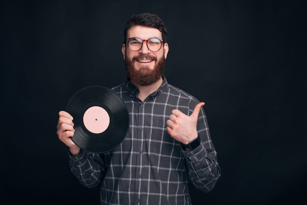 A bearded man holds a round vinyl record and shows a thumb up near black wall.
