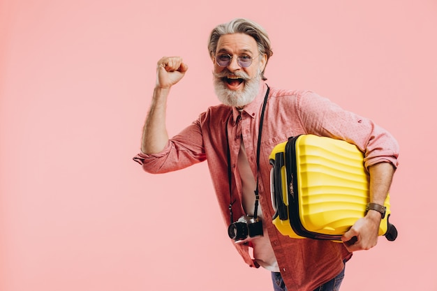 A bearded man holds a yellow suitcase, smiles and prepares for the trip.