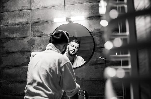 バスルームのバスローブでひげを生やした男。新郎の朝はホテルでの結婚式の準備をします。男のファッション写真。
