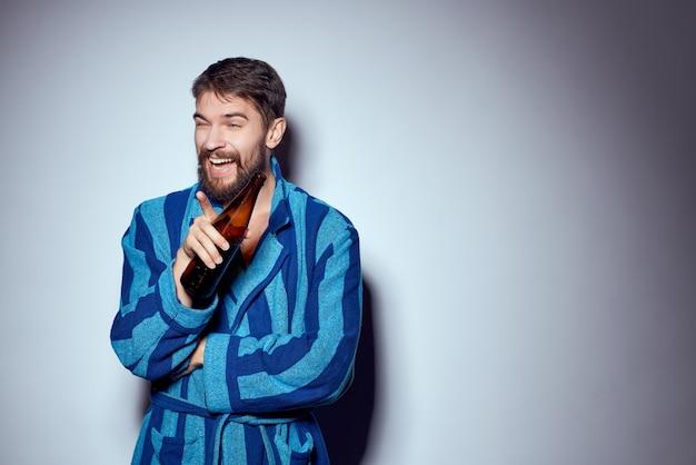 Бородатый мужчина в синем халате и с бутылкой пива. фото высокого качества