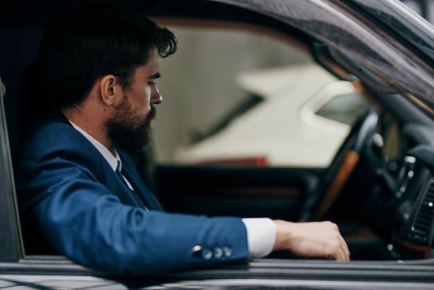 도시를 운전하는 자동차 정장에 수염 난 남자