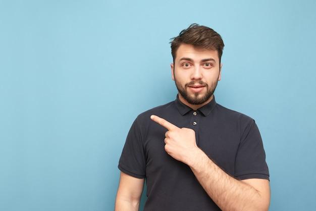 暗いtシャツを着たひげを生やした男は青の上に立って、彼の指を脇に、空のスペースを示しています