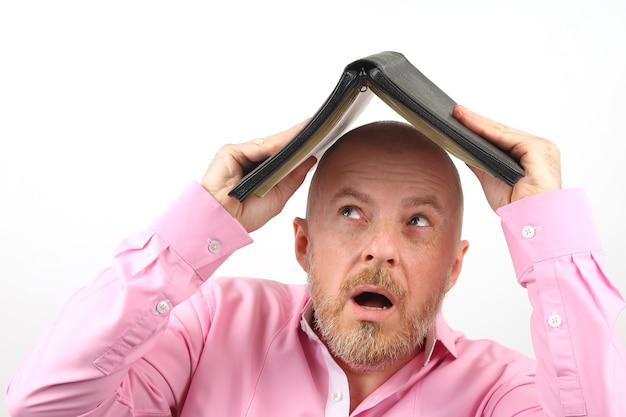 분홍색 셔츠에 수염 난 남자가 열린 성경 아래에 그의 머리를 숨 깁니다