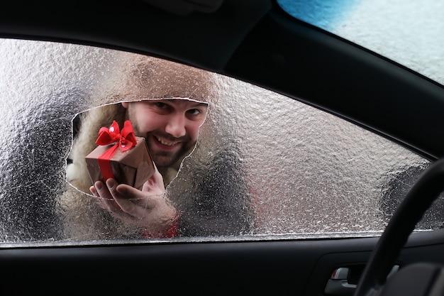 Бородатый мужчина в красной фуражке деда мороза в машине с битым стеклом