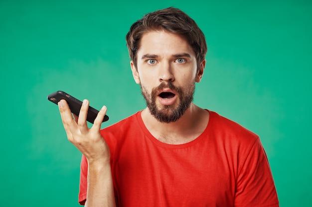 彼の手に電話と緑の背景を持つ赤いtシャツのひげを生やした男
