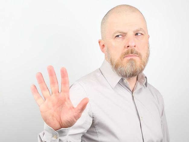 不愉快な表情と否定的な感情を持つシャツを着たひげを生やした男
