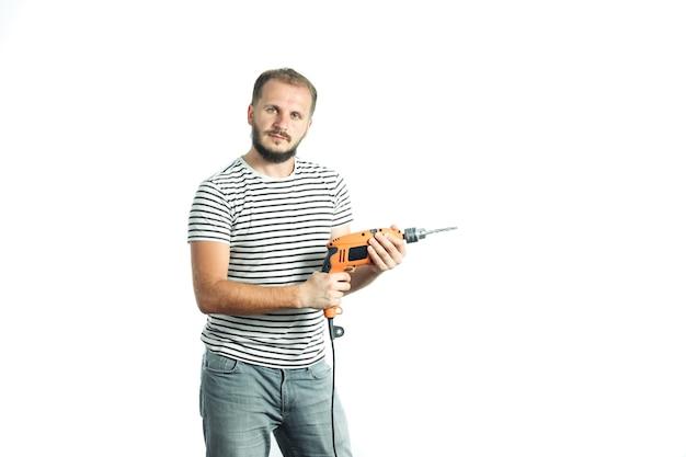 縞模様のtシャツのひげを生やした男は彼の手で電動工具の電気ドリルを保持します白で隔離
