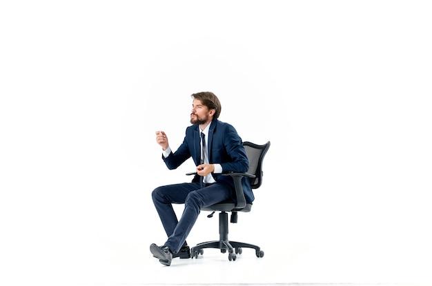 オフィスの椅子の仕事の明るい背景に座っているスーツのひげを生やした男