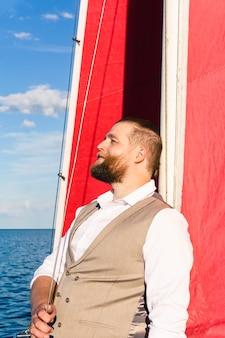 조끼를 입은 수염 난 남자는 바다에서 요트를 행복한 미소로 돛대에 기대어