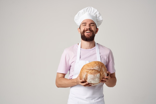 손에 빵을 들고 밝은 배경을 굽고 있는 흰색 앞치마를 입은 수염 난 남자