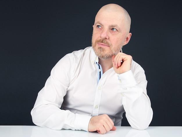 Бородатый мужчина в белой рубашке сидит за белым столом