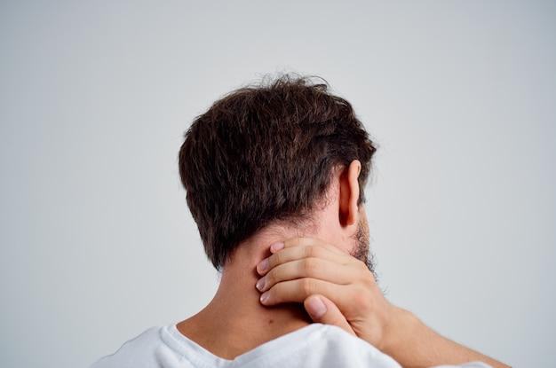 白いtシャツのひげを生やした男は、首の明るい背景の薬の痛みを強調します。高品質の写真